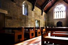 Старая архитектура церков с каменными стенами и деревянными скамьями стоковое фото