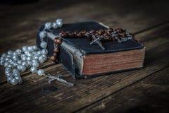 Старая библия с католическим розарием на таблице Стоковая Фотография