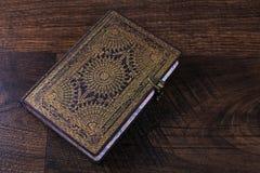 Старая богато украшенный тетрадь на деревянной предпосылке Стоковое Изображение