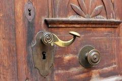Старая бронзовая ручка двери на украшенной деревянной двери Стоковое Фото