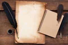 Старая бумага на коричневой деревянной текстуре с пером и чернилами, пустой тетрадью стоковые изображения