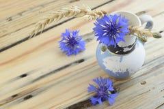 Старая ваза с cornflowers и ушами пшеницы стоковое изображение