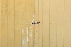 Старая дверь амбара сделанная из древесины покрасила желтое запертое с padlock и цепью стоковая фотография
