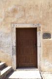 Старая дверь в каменных стенах домов в деревне предпосылка превосходная Стоковые Фотографии RF