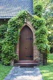 Старая дверь церков покрытая с плющом Стоковые Изображения RF