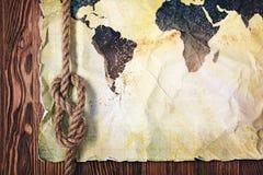 Старая винтажная карта мира на желтой ретро запятнанной бумаге с узлом веревочки Стоковое Изображение