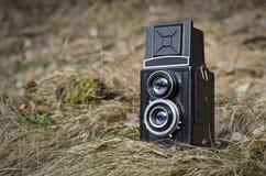 Старая винтажная сетноая-аналогов камера фото в предпосылке травы природы стоковое изображение