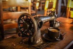 Старая винтажная швейная машина с кофейной чашкой на таблице деревни Стоковые Фотографии RF