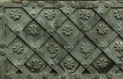 Старая выкованная текстура металла с декоративными верхними слоями Двери, стробы, штарки Деталь средневековой серой двери с decor стоковые изображения rf