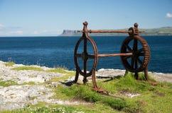 Старая вытравленная железная моталка с cogwheel, рядом с морем, ирландское побережье Стоковые Изображения RF