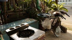 Старая газовая плита с винтажными утварями кухни в саде стоковое изображение