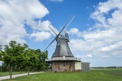 Старая голландская ветрянка на ландшафте с деревьями и голубым небом Стоковое Изображение