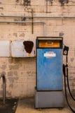 Старая голубая бензиновая колонка перед worn белой кирпичной стеной стоковые фото