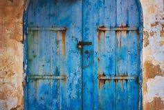 Старая голубая деревянная деревенская покрашенная дверь в сельской местности с металлом прикрепляет на петлях с ржавчиной стоковые фотографии rf