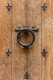 Старая деревянная входная дверь с ручкой и ironwo fleur-de-lis Стоковое Изображение