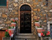 Старая деревянная дверь украшенная с цветочными горшками и шагами в средневековое Стоковые Фотографии RF