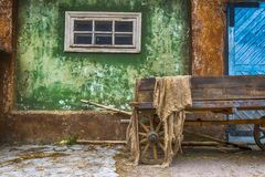Старая деревянная тележка в деревне на предпосылке старого дома Большой голубой деревянный строб стоковое фото rf
