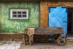 Старая деревянная тележка в деревне на предпосылке старого дома Большой голубой деревянный строб стоковые фото