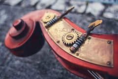 Старая деталь виолончели деталей mahogany и латуни Siz на предпосылке старых pavers Деревянная часть двойного ба стоковая фотография