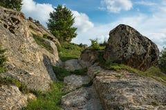 Старая дорога с автошиной отслеживает налево на камни стоковые изображения rf
