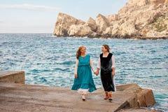 Старая дочь матери и взрослого в ретро старомодных одеждах держа руки идя и говоря на каменном пляже голубого моря Стоковые Фотографии RF