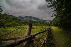 Старая деревенская загородка окруженная горами в дне дождевых облако Стоковые Фотографии RF