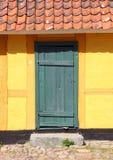 Старая деревянная дверь с красными плитками и желтой стеной Стоковая Фотография