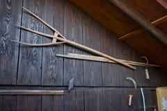 Старая деревянная вила и серпы на старом амбаре Стоковые Фотографии RF