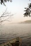 Старая деревянная шлюпка на пляже и туманном озере Стоковые Фото