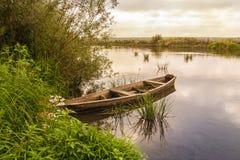 Старая деревянная шлюпка около берега реки Стоковая Фотография RF