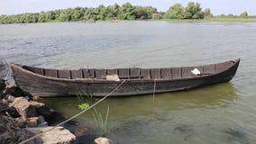 Старая деревянная шлюпка причаленная в реке акции видеоматериалы