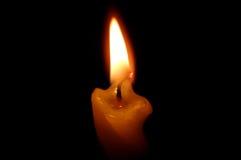 Старая желтая свечка на черноте. Стоковые Изображения