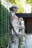Старая женщина мраморной статуи с корзиной цветков в парке Стоковые Изображения RF