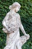 Старая женщина мраморной статуи с корзиной цветков в парке Стоковая Фотография RF