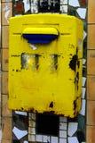 Старая желтая смертная казнь через повешение почтового ящика на кирпичной стене дома в v Стоковое фото RF