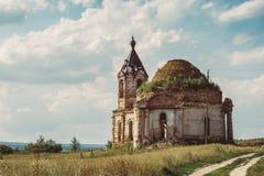 Старая загубленная русская церковь или висок перерастанные с травой среди поля стоковое изображение rf