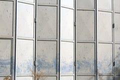 Старая и поврежденная дверь складчатости металла серая на покинутом складе стоковая фотография