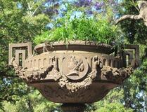 Старая каменная ваза с травой в парке города Стоковая Фотография