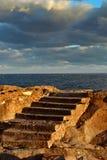 Старая каменная лестница в утесе на предпосылке горизонта моря Стоковое Изображение