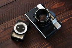 Старая камера и античный светлый метр на коричневом деревянном backgro стоковая фотография rf