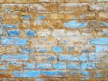Старая кирпичная кладка, запачканная погодой, голубой и желтой покрашенной стеной Стоковые Фотографии RF
