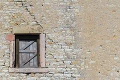 Старая кирпичная стена со старыми деревянными шторками окна стоковые фото