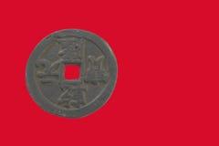 Старая китайская монетка с красной предпосылкой Стоковые Фотографии RF
