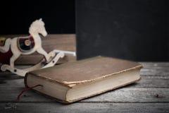 Старая книга и деревянная лошадь игрушки Стоковая Фотография RF