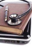Старая книга на черной компьтер-книжке Стоковые Фото