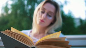 Старая книга перед привлекательным чтением студента девушки в парке видеоматериал