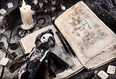 Старая книга с произношениями по буквам зла, страшной куклой, rune и свечой горения на планках стоковое фото rf