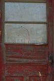 Старая красная дверь на покинутом здании Стоковые Изображения