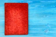 Старая красная закрытая винтажная книга изолированная на голубом backdrown с космосом экземпляра Стоковые Фото