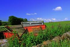 Старая красная тележка фермы в поле Стоковое Изображение RF